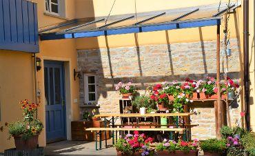 Liebevoll hergerichtete Veranda des Geschäfts- und Wohnhauses