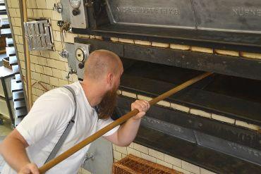 Bäckermeister Matthias Distler schießt mit Brotschieber Gebäck in den Ofen ein