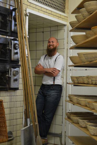 Bäckermeister Matthias Distler umgeben von Backofen, Garraum und Brotkörben